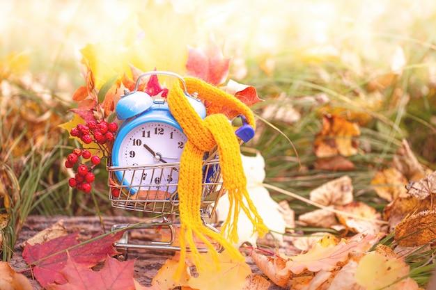 Vintage wekker met een sjaal en esdoorn bladeren in de herfst bos Premium Foto