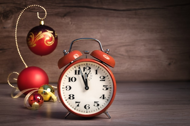 Vintage wekker met vijf tot twaalf en kerstballen op hout.