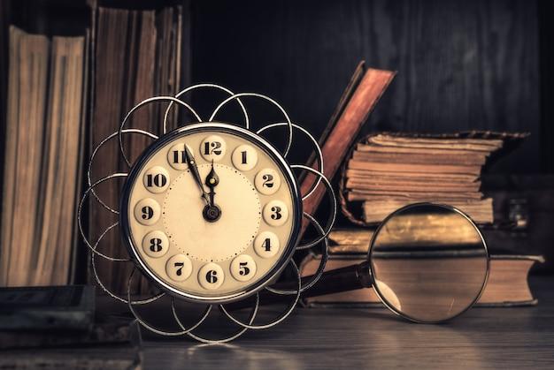 Vintage wekker met vijf tot twaalf onder oude boeken