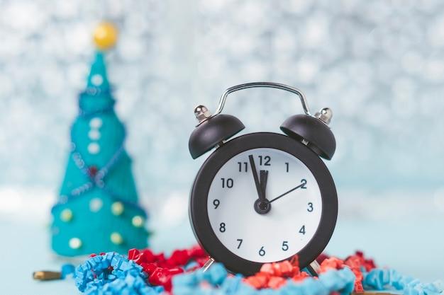 Vintage wekker op de achtergrond van de bokeh van het nieuwe jaar.