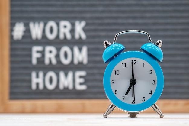 Vintage wekker op de achtergrond van engelse tekst werk vanuit huis. concept van werken op afstand tijdens de coronaviruspandemie covid-19