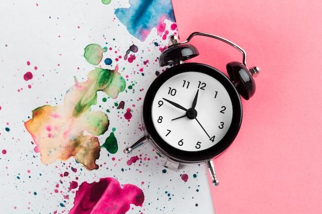 Vintage wekker op een creatieve kleurrijke achtergrond met verf hagelslag