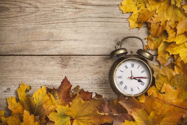 Vintage wekker op houten achtergrond met gouden herfstbladeren