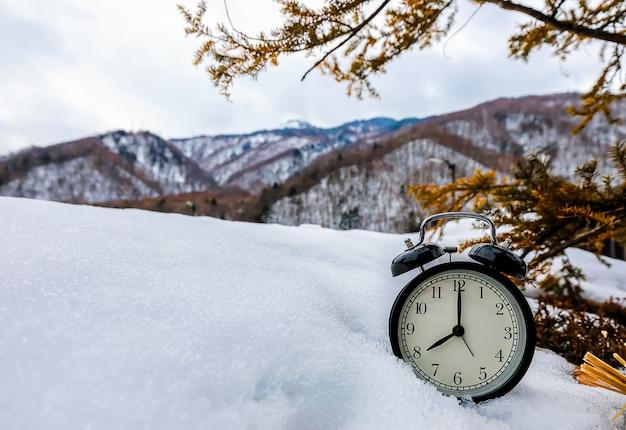 Vintage wekker op sneeuw met boom en bergen in de ochtend.