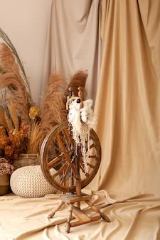 Vintage werktuigmachine - spindel, een apparaat voor het met de hand spinnen van garen. oud houten spinnewiel met garen in houten huisbinnenland. vintage gereedschap en natuurlijke wol om ecologische kleding te maken. rustiek, boho