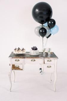 Vintage witte houten tafel met kasten, verjaardagstaart, desserts, martini glazen en zwarte, blauwe en grijze lucht ballonnen, geïsoleerd op een witte achtergrond. vakantie, verjaardagsfeestje concept