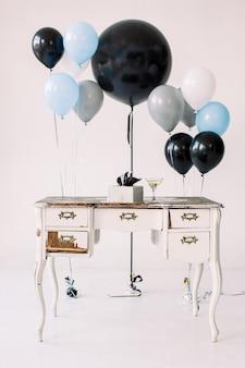 Vintage witte houten tafel met kasten, verjaardagstaart, martiniglas en zwarte, blauwe en grijze lucht ballonnen, geïsoleerd op een witte achtergrond. vakantie, verjaardagsfeestje concept