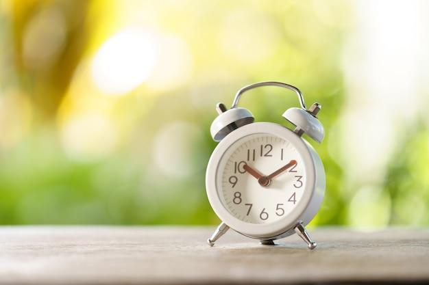 Vintage witte wekker op hout. het is tijd om te rusten. gebruiken als achtergrond ontspannende tijd