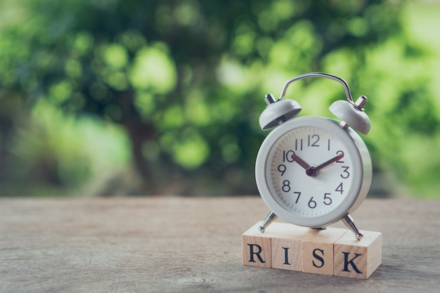 Vintage witte wekker op hout woord risico geplaatst. het concept van risico