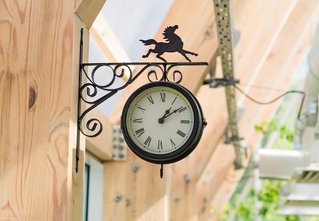 Vintage zwarte klok met gepord paard op de houten paal.