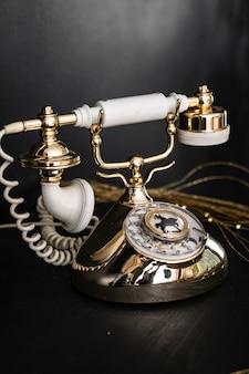 Vintage zwarte telefoon op oud een houten tafel achtergrond