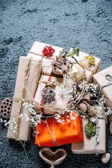 Vintages kerstcadeaus met bloemen, hout en rood en goud touw