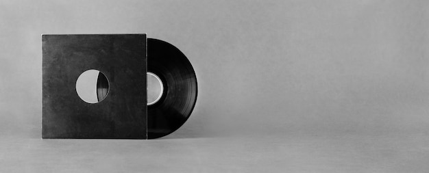 Vinyl audioschijf in zwarte document envelop die op abstracte grijze achtergrond wordt geïsoleerd