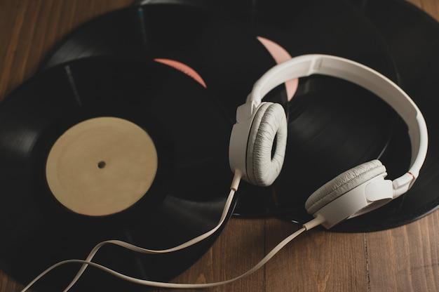 Vinylplaten op een houten achtergrond en witte koptelefoons