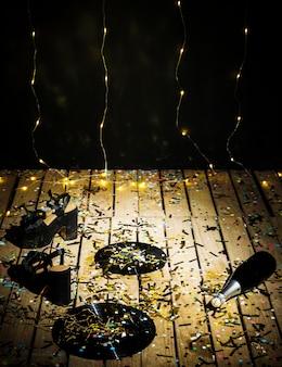 Vinylverslagen, vrouwenschoenen en fles drank tussen confettien dichtbij muur