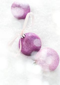 Violet balls met een strik van lint in de sneeuw