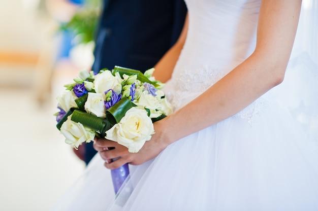 Violet huwelijksboeket op hand van bruid achtergrondbruidegom