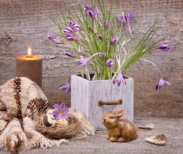Violet krokussenboeket, kwartelseieren in het natuurlijke stronest, konijn en aangestoken kaars op hout