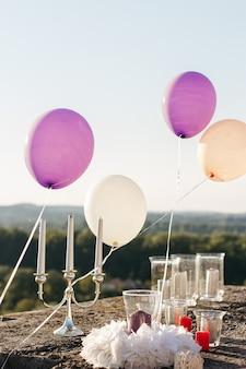Violette en witte ballonnen zweven over de kaarsen