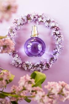 Violette fles parfum voor vrouwen naast de bloemen van lila