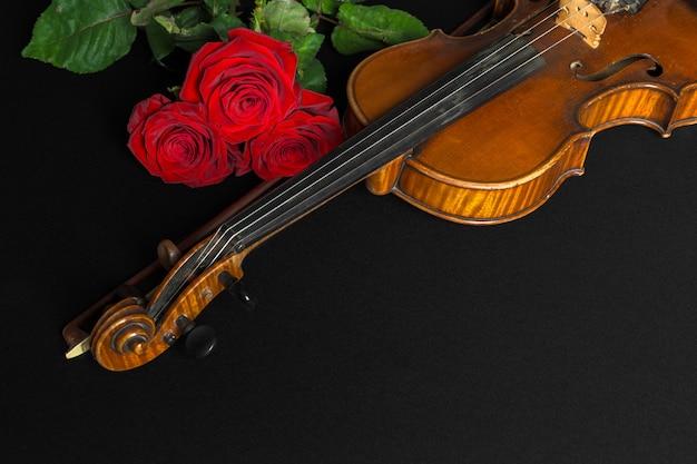 Viool en roos op zwarte achtergrond.
