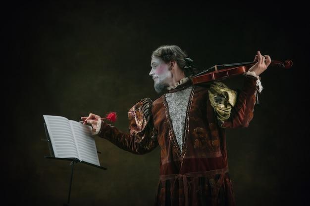 Viool spelen jonge man als johann bach geïsoleerd op donkergroene achtergrond