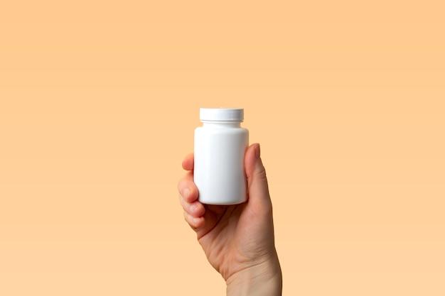 Virale ziekte preventie concept. vrouwelijke hand houdt pot met vitamines, pillen, medicijnen of drugs op oranje achtergrond. coronaviruspreventie. veiligheidsregels tijdens quarantainetekst