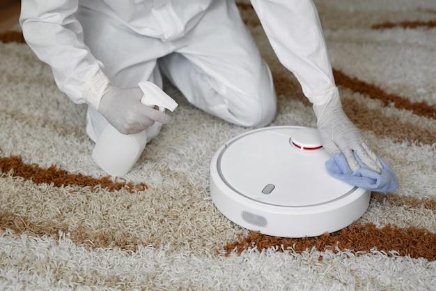 Virologen, mensen in beschermende pakken voeren de desinfectie in het appartement uit. veeg de robotstofzuiger schoon tijdens de coronavirusepidemie. covid-19