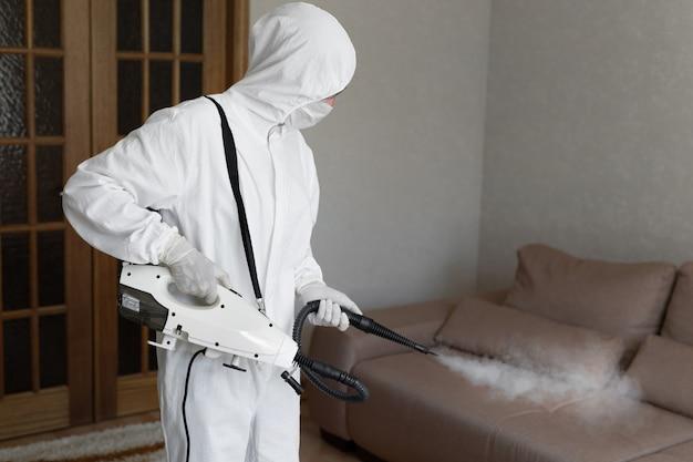 Viroloog in beschermend hazmat-pak voert desinfectie van oppervlakken uit