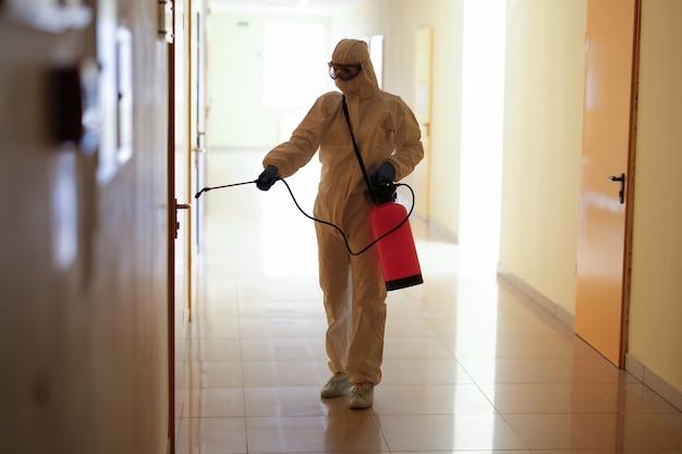 Viroloog in beschermend hazmatpak desinfecteert oppervlakken in openbare en geïsoleerde ruimtes. pandemisch gezondheidsrisicoconcept