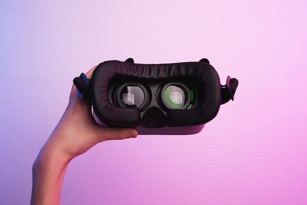 Virtual reality-bril in de hand op de kleurrijke achtergrond. toekomstige technologie, vr-concept