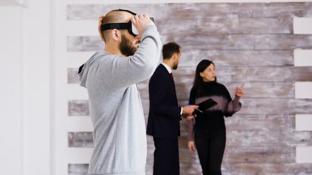 Virtual reality ervaren met headset in nieuw appartement en vrouw in gesprek met makelaar op de achtergrond.