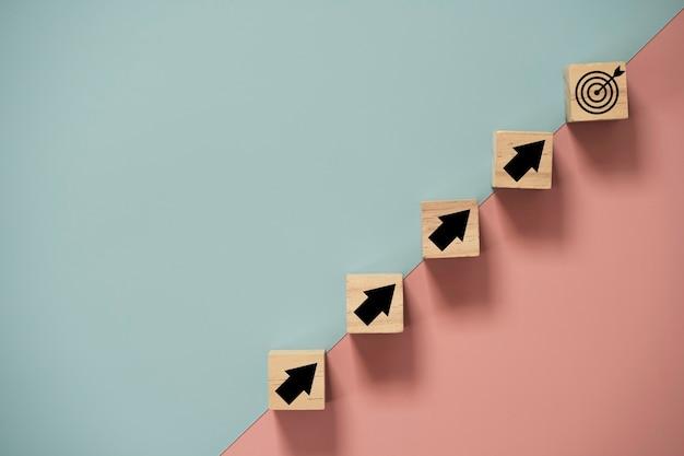 Virtueel doelbord en pijl die scherm afdrukken naar houten kubusblok op blauwe en roze achtergrond. bedrijfsdoelstelling en objectief doelconcept.