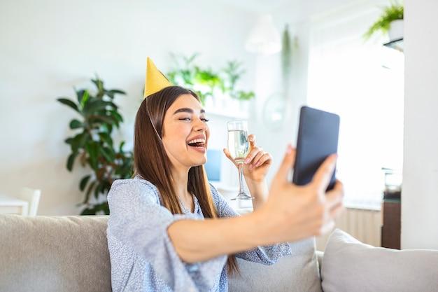 Virtueel feest. gelukkige jonge vrouw met hoed die online videoconferentie heeft met vrienden en familie, een glas wijn vasthoudt, roostert en verjaardag viert, thuis blijft