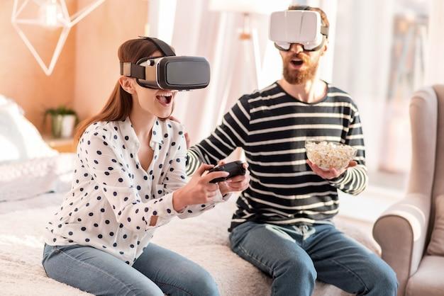 Virtueel spel. krachtige optimistische prachtige vrouw schreeuwen zittend op bed en spelen in vr-spel