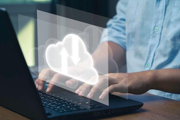 Virtuele cloud en technologiepictogrammen, zakenman die laptop computer gebruikt om verrichtingen via cloud computing-systeem te controleren.