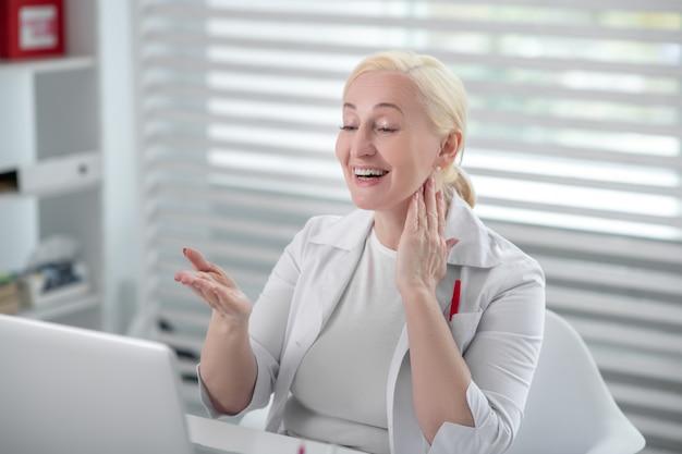 Virtuele dokter. glimlachende vrouw in een witte laag die haar hand aan het scherm standhoudt bekijkend blij laptop ,.