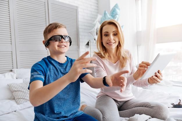 Virtuele realiteit. blij leuke positieve vrouw zittend op het bed en met behulp van een tablet tijdens het spelen met haar zoon
