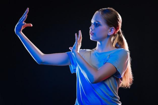 Virtuele realiteit concept. aardige serieuze vrouw die haar handen beweegt tijdens het gebruik van virtueel technologisch apparaat