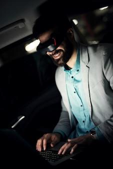 Virtuele realiteit concept. zakenman in de auto die laat werkt.