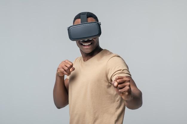 Virtuele realiteit. jonge volwassen donkere gespierde man met virtuele bril hand in hand in vuisten