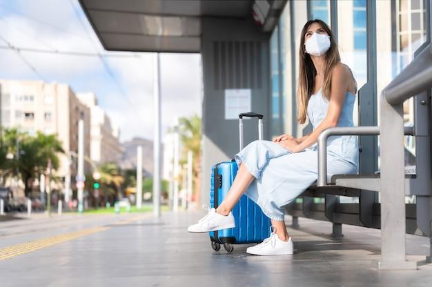 Virusbescherming in het openbaar vervoer. vrouw die beschermend masker draagt. virus pandemie en vervuiling concept. vrouw te wachten op het treinstation.