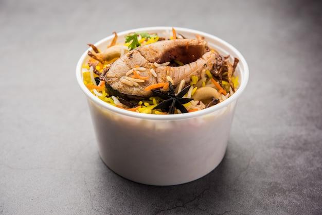 Vis biryani of pulao in restaurantstijl verpakt voor thuisbezorging in plastic doos of container met raita en salan