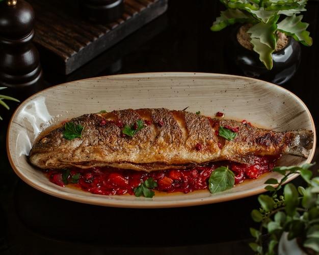 Vis gebakken in granaatappelsaus en geserveerd in granaatplaat
