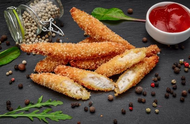 Vis gebakken nuggets op een zwarte stenen bord met saus