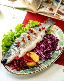Vis gegarneerd met granaatappel en salade