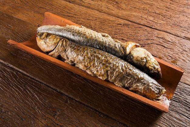 Vis geroosterd op de tegel op oude houten tafel