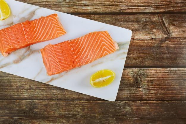 Vis heerlijke rauwe zalmfilet met plakjes citroen op een marmeren bord