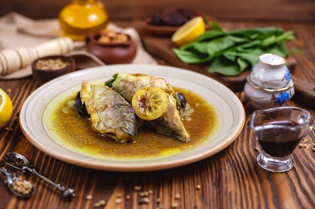 Vis in olieachtige saus spinazie citroen kruiden zijaanzicht