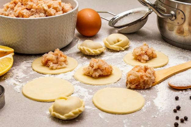 Vis knoedels. ingrediënten voor thuis koken. vers deeg, vis, kruiden, kookgerei.